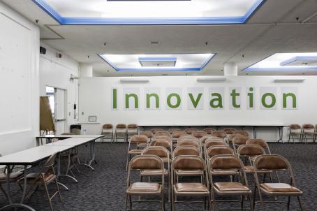 Huone, jossa on ruskeanahkaisia taittotuoleja monessa rivissä. Tilassa on sinisävyinen kokolattiamatto, sivuilla on pöytiä ja takaseinällä lukee Innovation.