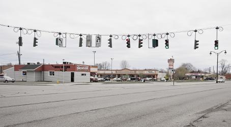Tie, jonka yli menee vaijeri, jossa roikkuu monta liikennevaloa ja liikennemerkkejä. Taaempana näkyy kauppoja.
