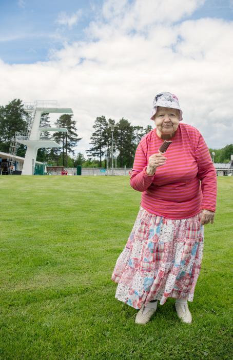 Vanha nainen seisoo nurmikolla vaaleanpunaraitaisessa paidassa ja vaaleanpunaisessa hameessa ja syö tikkujäätelöä. Taustalla näkyy uimahyppytorni.