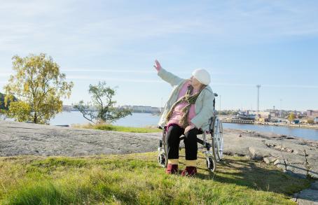 Pyörätuolissa oleva vanha nainen rantakalliolla. Taustalla näkyy rakennuksia ja satamaa. Nainen on nostanut kätensä ylös sivulleen ja katsoo samaan suuntaan.