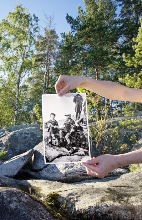 Kallioita metsässä. Kädet pitelevät kallion edessä mustavalkoista valokuvaa, jossa pojat istuvat soittamassa samalla kalliolla kuin mikä taustalla on. Kuva on aseteltu niin, että kallion linjat täsmäävät.