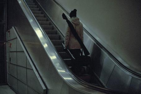 Mies seisoo selin liukuportaissa menossa ylöspäin. Hänellä on selässään pitkänomainen laukku ja hän kantaa käsissään mustia laukkuja.