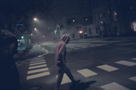 Huppupäinen poika kävelee vesisateessa suojatien yli yön hämärässä. Etualalla näkyy myös osittain toinen ihminen.