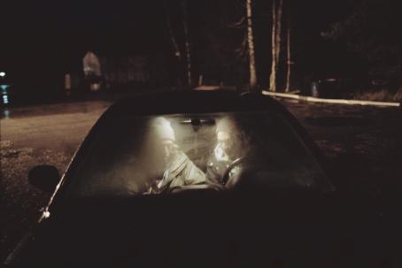 Auto, jonka huuruisen tuulilasin takana istuu kaksi poikaa.
