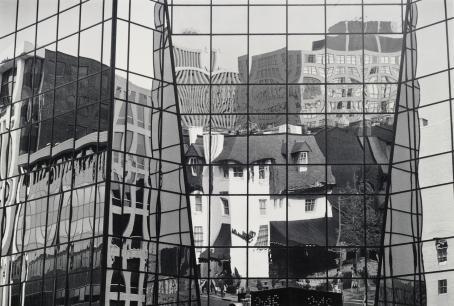 Kuva-alan täyttää lasiruuduista koostuva seinä, joka heijastaa sitä vastapäätä olevia rakennuksia ja vääristää niitä.
