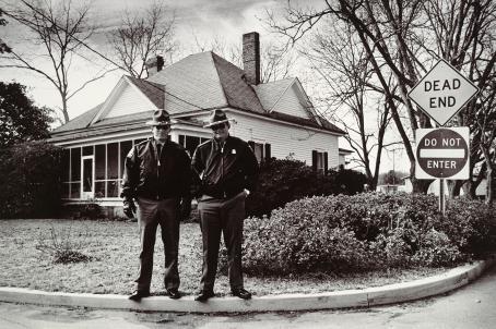 """Mustavalkoisessa kuvassa talon edessä, tien vieressä seisoo kaksi samalla tavalla pukeutunutta miestä. Heillä on mustat suorat housut, tumma takki, aurinkolasit ja hattu. Tien varressa on kaksi liikennemerkkiä, joissa lukee """"Dead end"""" ja """"Do not enter""""."""