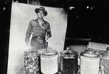 Mustavalkoisessa kuvassa isoja lasisia karkkipurkkeja rivissä. Niiden takana kuva cowboysta ase kädessä.