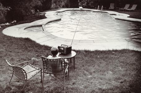 Mustavalkoisessa kuvassa uima-allas. Altaan vieressä nurmikolla istuu tuolissa lapsi kuuntelemassa pöydällä olevaa radiota.