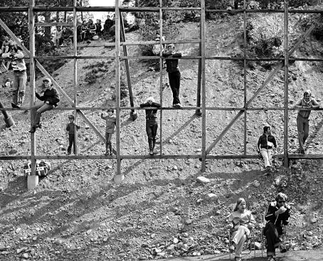 Mustavalkoisessa kuvassa soraisessa mäenrinteessä on iso puinen kehikko. Kehikossa on lapsia seisomassa ja istumassa poikkipuilla. Ylhäällä rinteen päällä on lisää ihmisiä, alhaalla kaksi ihmistä istuu tuoleilla.