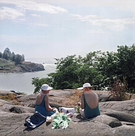 Kaksi naista istuu rantakallioilla. Toisella on uimapuku ja toisella mekko, heillä on valkoiset hatut päässä. Aurinko paistaa ja takana näkyy meri.