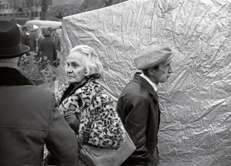 Mustavalkoisessa kuvassa etualalla kaksi ihmistä keskustelevat. Vanhalla naisella on leopardikuvioinen turkistakki, mies on selin. Heidän takanaan kävelee mies.