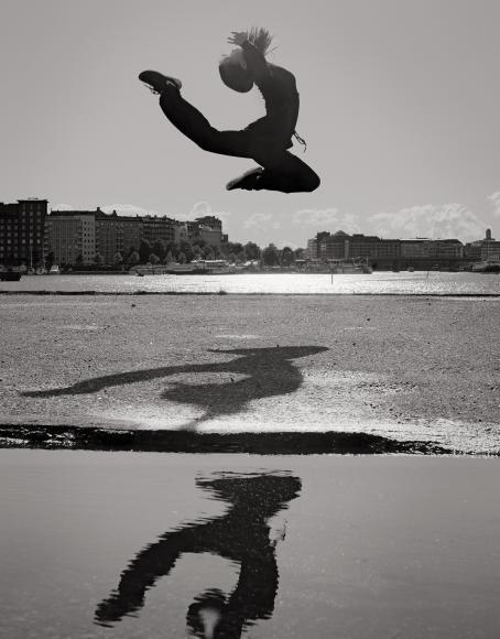 Mustavalkoisessa kuvassa henkilö on ilmassa, hän on hypännyt taivuttaen ylävartaloaan taaksepäin ja jalkaansa päätä kohti. Hänen varjonsa näkyy maassa hänen allaan ja kuvan etualalla olevassa vedessä. Taustalla näkyy merenlahti ja kerrostaloja.