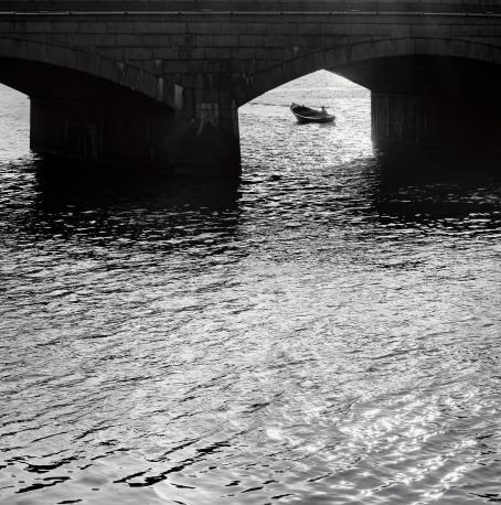 Mustavalkoisessa kuvassa etualalla on vettä, kuvan yläosassa näkyy osittain silta. Sillan alta kauempana näkyy vene.