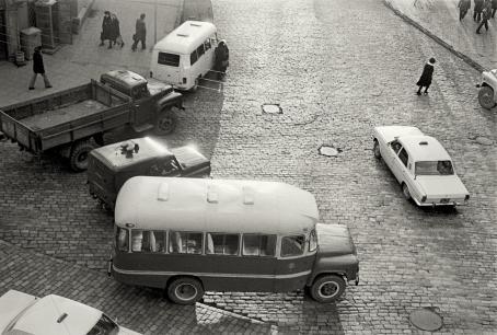 Mustavalkoisessa kuvassa ylhäältäpäin kuvattu tien risteys, jossa ajaa pieni vanhanaikainen bussi ja muita autoja.