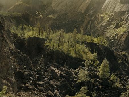 Maisema, jossa molemmin puolin korkeat kallioseinämät, keskellä kalliolla kasvaa metsää, jonka alapuolella suuria kivilohkareita.