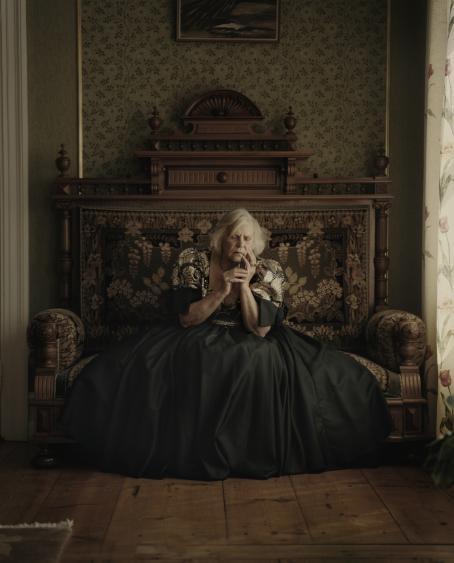Vanha nainen istuu koristeellisella sohvalla, hänellä on päällään mekko jonka helma on lähes koko sohvan levyinen. Hän nojaa hieman päätään sormiinsa ja hänellä on silmät kiinni.