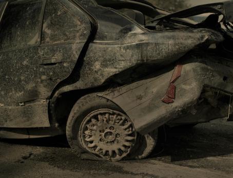 Kärsinyt auton takaosa. Rengas on lytyssä, auto on likainen ja auto näyttää siltä kuin sen perään olisi törmännyt joku.