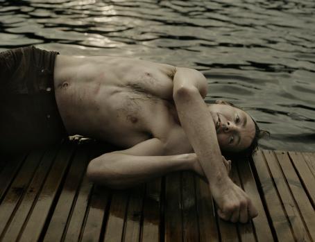 Mies makaa laiturin reunalla. Hänellä on mustat housut mutta ei paitaa, ja hänen ihonsa on märkä.
