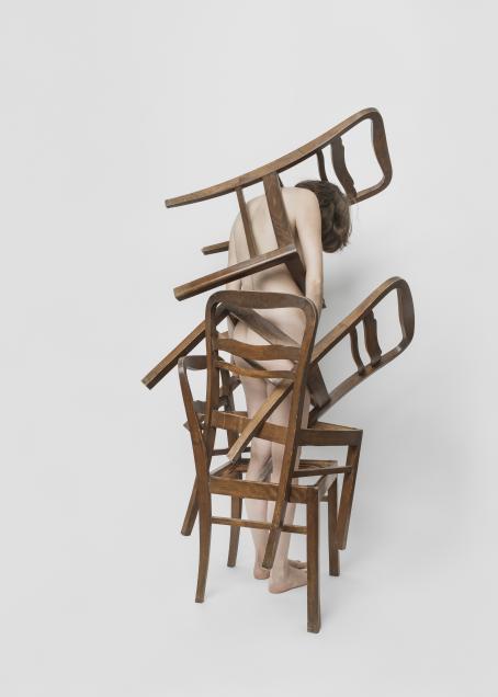 Valkoista taustaa vasten alaston nainen seisoo selin kameraan, pää painuksissa. Hänen ympärillään on puisia ruskeita tuoleja, hän seisoo niiden sisällä. Yksi on hänen hartioidensa ympärillä.