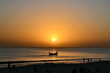 Auringonlaskun oranssiksi värjäämä taivas, jonka alla meri. Meren yllä lentelee lokkeja, ja melko lähellä rantaa menee vene, jossa olevat ihmiset näkyvät mustina siluetteina. Horisontissa näkyy heikosti kaupungin ääriviivat. Lähimpänä on ranta, jossa olevat ihmiset näkyvät myös siluetteina.