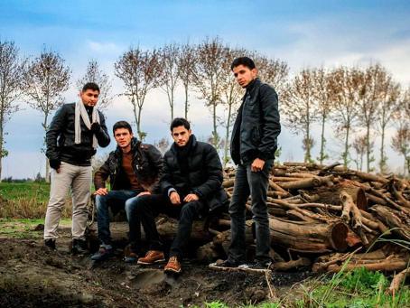 Neljä miestä puukasan edessä. Kaksi keskimmäistä istuu katkaistun puunrungon päällä, kaksi reunoilla olevaa seisoo.
