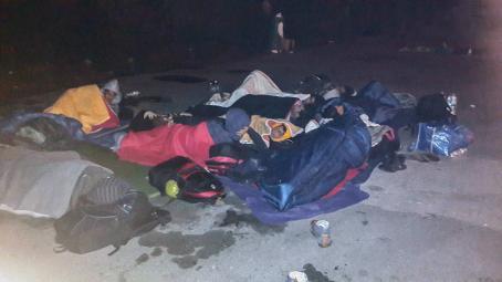 Pimeällä otettu kuva jossa ihmisiä nukkuu makuupusseissa maassa. Heidän ympärillään on reppuja ja laukkuja.