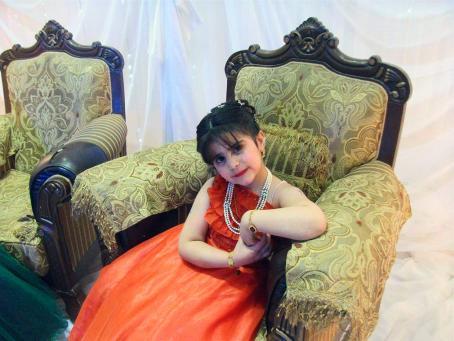 Pieni tyttä punaisessa mekossa istuu koristeellisessa vihreässä nojatuolissa. Tytöllä on kaulakoru ja rannekorut.