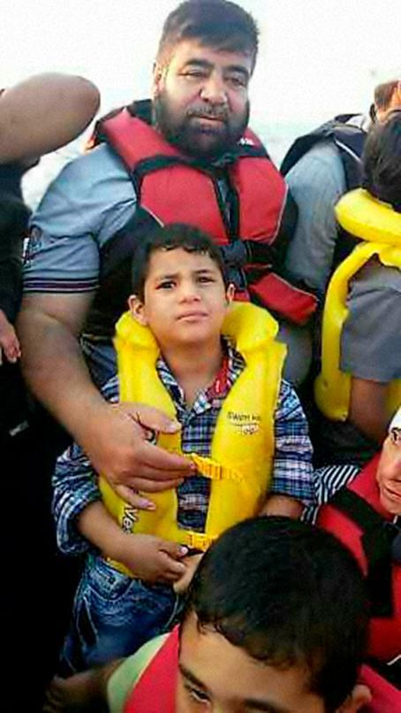 Mies ja poika. Miehellä on punainen pelastusliivi ja pojalla keltainen. Mies pitää kättään pojan rinnalla. Kuvassa näkyy myös osittain muita ihmisiä joilla on pelastusliivit.