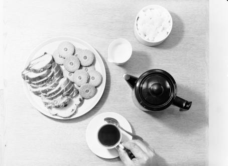 Mustavalkoisessa, ylhäältäpäin otetussa kuvassa on kahvipöytä. Käsi pitelee lautasen päällä olevaa kahvikuppia, lisäksi pöydällä on tarjoiluastiassa pullaa ja keksejä, sokeriastia, maito- tai kermakannu ja kahvipannu.