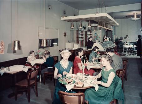 Näkymä kahvilasta sisältä. Etualalla pyöreässä pöydässä istuu kaksi nuorta naista mekot päällä. Toinen voitelee leipää. Taaempana näkyy lisää pöytiä ja kahvilan tiski.