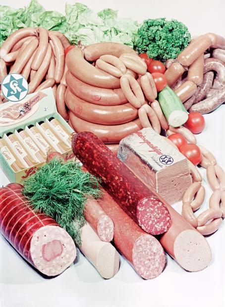 Pöydällä on esillä erilaisia makkaroita, maksapasteijapaketti, kurkku, tomaatteja, salaattia, sinappituubeja laatikossa.