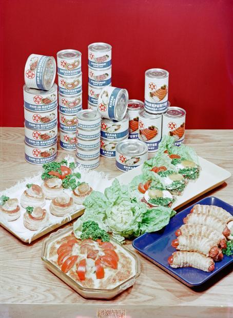 Pöydällä on taaempana pinoissa erilaisia säilykeruokatölkkejä. Niiden edessä on esillä erilaisia ruokia.