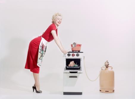 Kuvan keskellä on pieni kaasuhella, josta lähtee putki sen vieressä olevaan kaasupulloon. Toisella puolella on punaiseen mekkoon pukeutunut nainen, jolla on esiliina vyötäröllä ja hän nojaa käsillään hellaan. Hänellä on leveä hymy ja silmät kiinni.