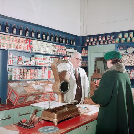 Nainen asioi kaupassa. Tiskin takana on mies, jonka takana hyllyillä on paljon erilaisia tavaroita. Tiskillä on iso vanhanaikainen vaaka.