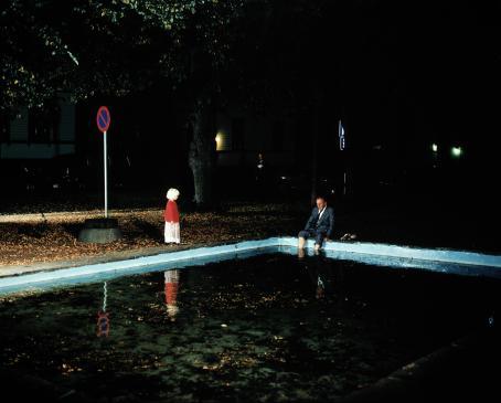 Mies istuu puku päällä uima-altaan reunalla ja uittaa jalkojaan vedessä. Vähän matkan päässä hänestä seisoo vaaleahiuksinen lapsi punaisessa paidassa.