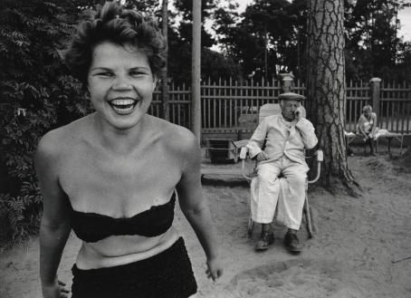Mustavalkoisessa kuvassa nainen bikineissä hymyilee ja taaempana istuu tuolissa vanhempi mies.