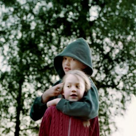 Lapsi jolla on vihreä huppari ja huppu päässä pitää kättään punapaitaisen lapsen ympärillä.