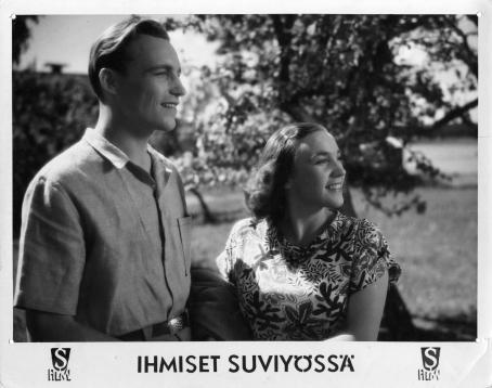 """Mustavalkoisessa kuvassa mies ja nainen katsovat samaan suuntaan. Alhaalla on teksti """"Ihmiset suviyössä""""."""