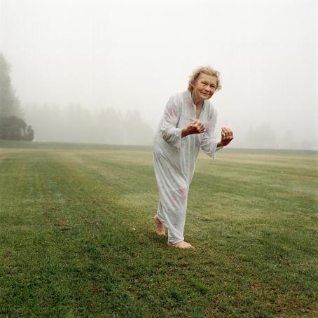 Vanhempi nainen tasaisella ruohikolla pitkä,vaalea yömekko päällään ja avojaloin. Hänen takanaan näkyy sumuista maisemaa.