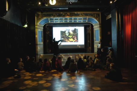 Lapsia istuu lattialla katsomassa lavalla olevia ihmisiä. Lavalle on heijastettu kuva josta ei oikein saa selvää ja sen edessä seisoo ihminen.