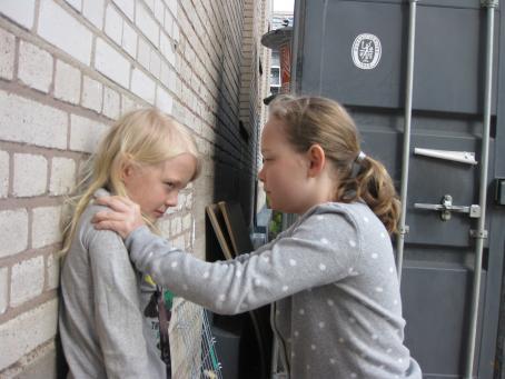 Lapsi pitää toista lasta seinää vasten hartioista kiinni.