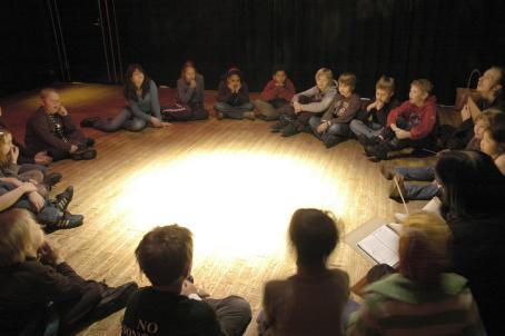 Lapsia istuu lattialla isossa ringissä. Heidän keskellään lattialla on iso valoympyrä, muuten huoneessa on melko hämärää.