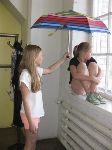 Tyttö istuu ikkunalaudalla polvet koukussa rintaa vasten ja katsoo ulos. Hänen vieressään seisoo toinen tyttö ja pitää värikästä sateenvarjoa ikkunalaudalla istuvan tytön pään päällä.