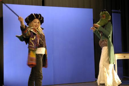Sinisen kankaan edessä on kaksi roolivaatteisiin pukeutunutta lasta. Toinen heilauttaa keppiä tai miekkaa.