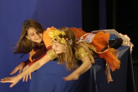 Kaksi roolivaatteisiin pukeutunutta lasta makaa mahallaan sinisellä kankaalla peitetyn ison laatikon päällä sinisen kankaan edessä. Heidän kädet ovat suorina edessä ja he hymyilevät.
