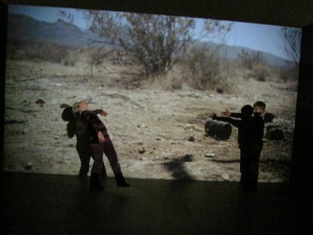 Seinälle on heijastettu kuva aavikosta. Sen edessä seisoo kaksi henkilöä. Toinen osoittaa etusormella toista pitäen peukaloa pystyssä, ja toinen nojaa taaksepäin kuin olisi kaatumassa.