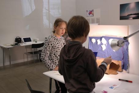 Kaksi lasta seisomassa pöydän ääressä. Toinen on selin kameraan, toinen katsoo mitä hän tekee. Pöydän keskellä on pystyssä jonkinlainen seinä, johon on kiinnitetty sininen kangas ja siihen valkoisia pumpulilta näyttäviä kappaleita.