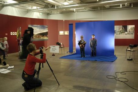 Ison tilan, ilmeisesti näyttelytilan, keskellä on pystyssä sininen kangas, jonka edessä seisoo kaksi lasta pukeutuneena roolivaatteisiin. Punapaitainen kuvaaja ottaa heistä kuvaa kolmijalalla olevalla kameralla.
