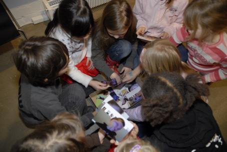 Lattialla istuu lapsia tiiviissä ringissä katsomassa paperisia valokuvia. Kuva on otettu ylhäältäpäin, joten lasten kasvoja ei näy.