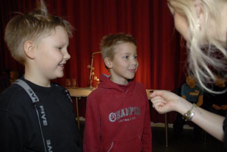 Kaksi nuorta poikaa seisoo vierekkäin. Pojat hymyilevät. Heidän edessään on vain osin kuvassa näkyvä nainen, joka pitää poikien edessä nyrkissä olevaa kättä ojennettuna.